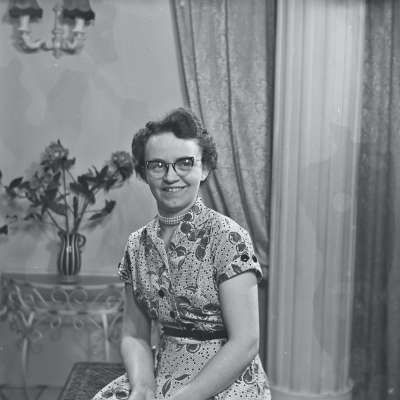 Portrait of woman in patterned dress and glasses