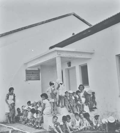 Group of  children and adults in front of building
